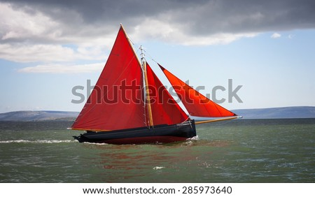 Traditional wooden boat Galway Hooker, with red sail, compete in regatta. Ireland. - stock photo