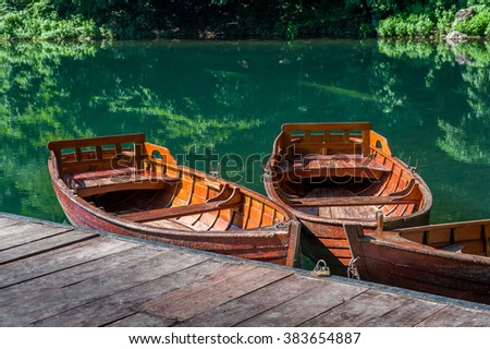 Traditional wooden boats at forest lake pier. Calm summer day. Biogradsko jezero national park, Montenegro