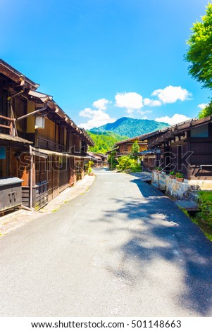 Traditional wooden buildings line the sides of the main street of Tsumago, an old post town on the ancient Nakasendo route during Edo period in Japan. Vertical