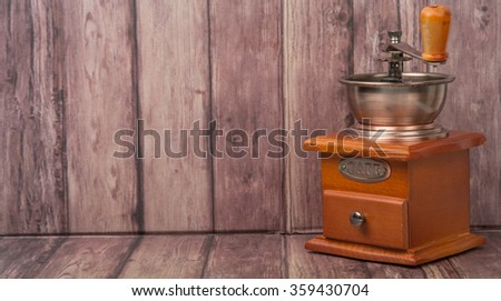 Traditional wooden coffee mill grinder over wooden background