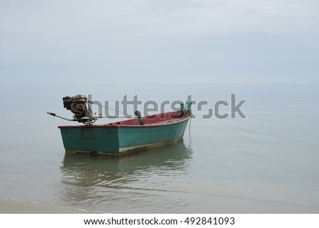 Traditional wooden fishing boat floating on the peace surface wave of the seas,in the afternoon against the blue waters,selective focus,minimalism