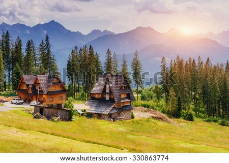 Traditional wooden house in the mountains on a green field Mountains, Poland. Europe - stock photo