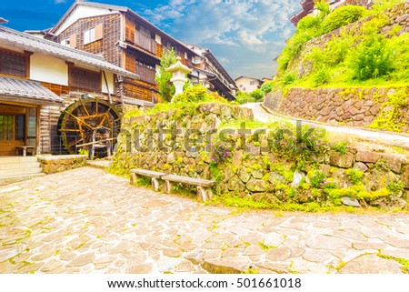 Traditional wooden houses and waterwheel line the stone path on this beautifully restored section of the historic Edo-period Nakasendo road in station town of Magome, Japan. Horizontal