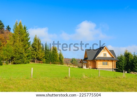 Traditional wooden mountain house on green field in Beskid Niski Mountains, Poland  - stock photo