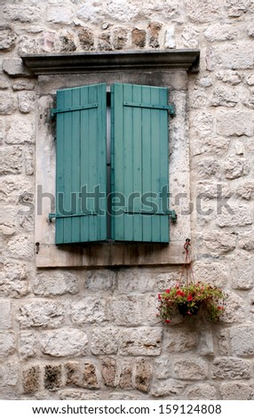 Traditional wooden shutters on small windows and stone wall