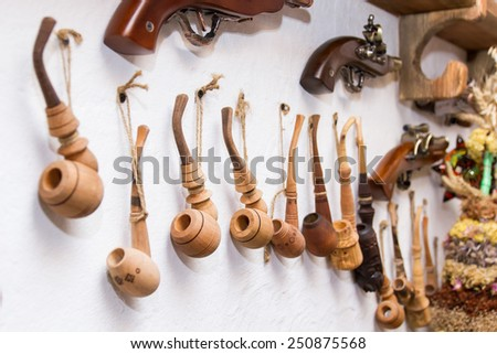 traditional wooden smoking tobacco pipe hanging on white wall - stock photo
