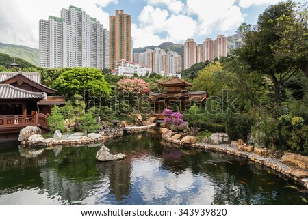 Traditional wooden teahouse and bridge by the pond at the Nan Lian Garden in Hong Kong, China. High-rise apartment buildings in the background.