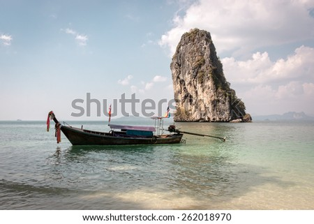 Traditional wooden Thai long-tail boat floating at the Andaman Sea near a rocky cliff island in Krabi, Thailand - stock photo