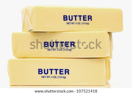 Traditional wrapped butter sticks on white background - stock photo