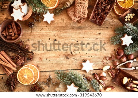 Traditional Xmas frame with spices, speculoos biscuits, star cookies and assorted nuts decorated with dried orange around central copyspace on a rustic wood background for your Christmas message - stock photo