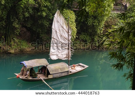 Traditional yacht boat along scenic river in Three Gorges.