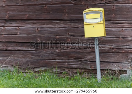 Traditional yellow postbox in front of a wooden wall, vintage style. Sweden - stock photo