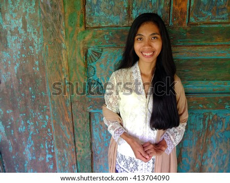 Traditional young Asian woman in front of wooden house.