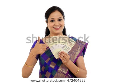 Traditional young woman holding Indian currency with thump up gesture