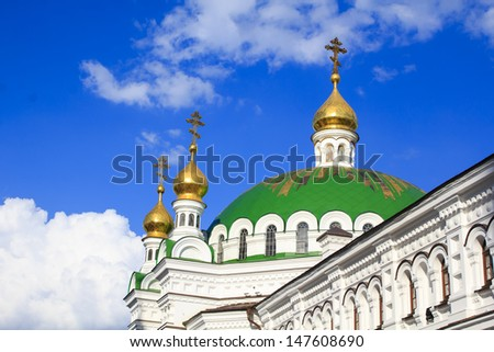 Traditionally green and golden domes of the Ukrainian cathedral against a bright blue sky with white clouds in famous Pechersk Lavra - one of the most visited by tourists places in Kiev, Ukraine - stock photo