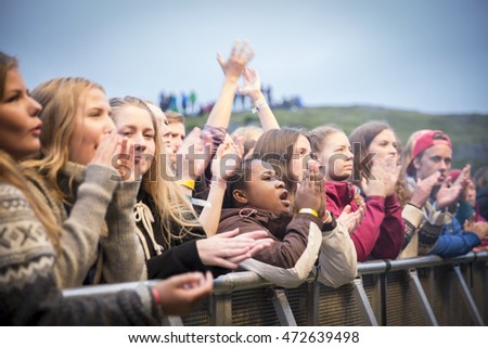 Traena, Norway - July 9 2016: audience cheering at concert of Norwegian musician and songwriter Bendik  at Traenafestival, music festival taking place on the small island of Traena