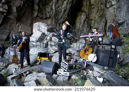 Traena, Norway - July 12 2014: concert of the Norwegian Singer Stein Torleif Bjella featuring Svartlamon Hardkor choir at Kirkehelleren cathedral cave, Sanna Island at the Traena music festival