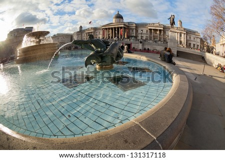 Trafalgar Square fountain in London, United Kingdom. Shot taken fisheye wide angle lens, which highlights the curvilinear architectural forms and round pool fountain in front - stock photo