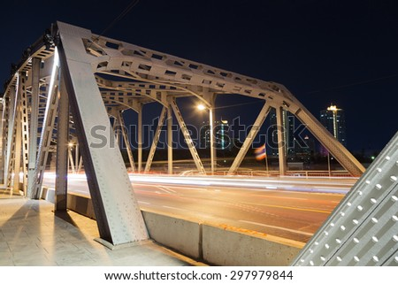 Traffic at night. The light from cars traveling across the bridge at night. - stock photo