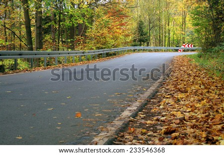 Traffic barrier on the mountain, winding road. Gold autumn forest. - stock photo