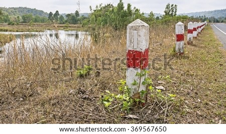 Traffic barrier red pillar sign on road with river and trees landscape A row of Red and white roadside pillars in a rural landscape  - stock photo