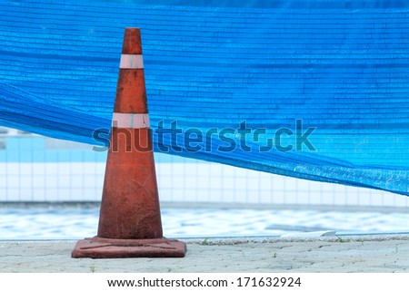 traffic cone near swimming pool repairing works - stock photo