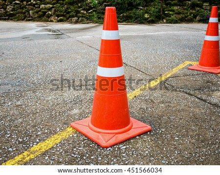 Traffic cone on the asphalt road with yellow line