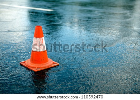 Traffic cone Traffic cone in the road on a rainy day - stock photo