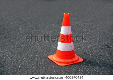 traffic cone, with white and orange stripes on gray asphalt, copy space - stock photo