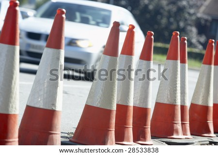 Traffic Cones Lined Up On The Side Of The Road - stock photo