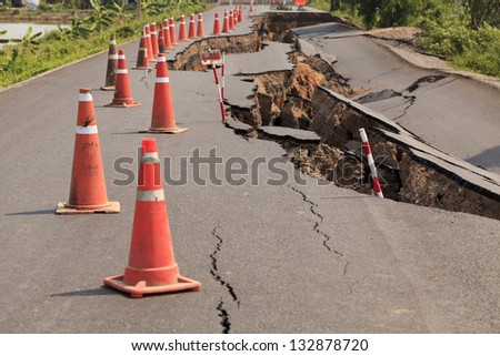Traffic cones on the cracked asphalt road - stock photo