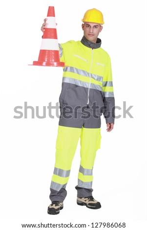 Traffic guard holding a pylon - stock photo
