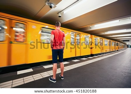Traffic in subway. Young man is waiting for subway. Berlin, Germany - stock photo