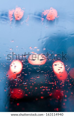 Traffic jam from inside a car during storm with rain drops on window. Shallow depth of field with focus on center of the windshield with red lights. - stock photo
