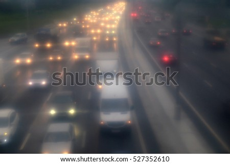 Traffic jam on highway. Many cars with bright headlights are staying in the fog in bad weather view in blur