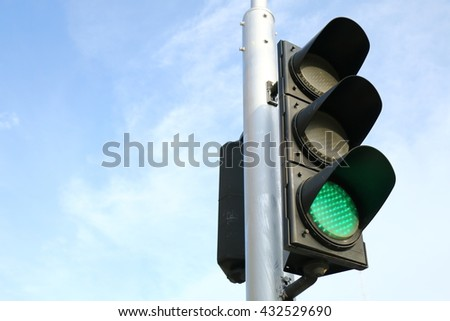 Traffic light and blue sky, green light symbolizes to go ahead - stock photo