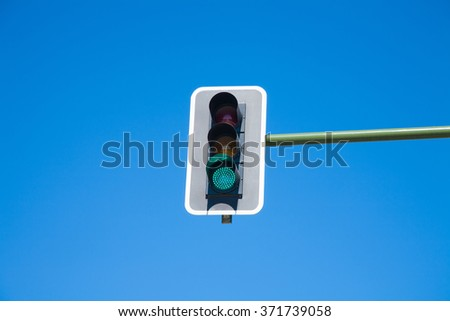 traffic light semaphore green light on orange and red lights off  in green pole on blue sky horizontal - stock photo