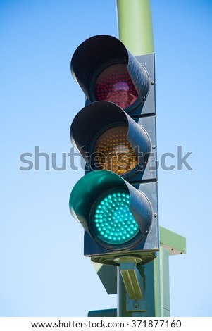 traffic light semaphore green light on orange and red lights off  in green pole on blue sky - stock photo