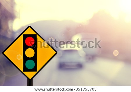 Traffic light sign on blur traffic road abstract background.
