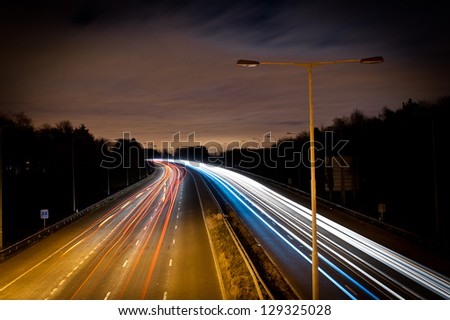 Traffic light trail at a busy highway - stock photo