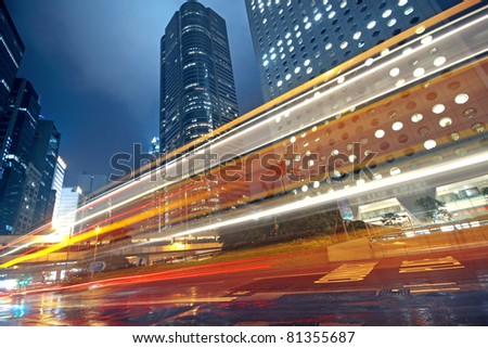 traffic light trails in the street by modern building