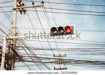 Traffic light with messy cable connection on the electric pole - stock photo