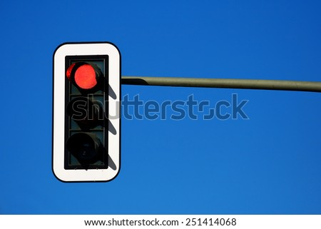 traffic lights against a vibrant blue sky - stock photo