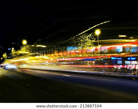 Traffic lights at night, shoot at low speed to get that blurred and trail effect. It's intentionally blurred to get the speed light effect - stock photo