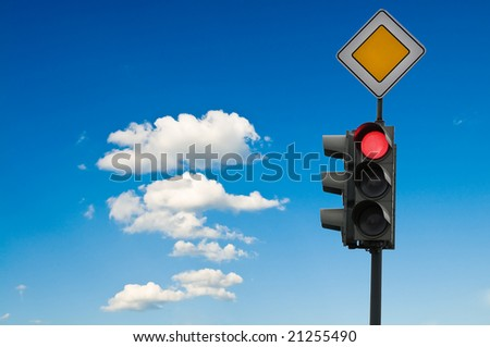 Traffic lights - on in front of blue sky - stock photo
