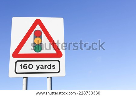 Traffic lights 160 yards ahead road sign with a light grey background against a clear blue sky.