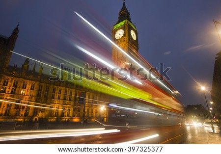 Traffic of cars and busses drives by Big Ben at Westminster Parliament in London in the evening