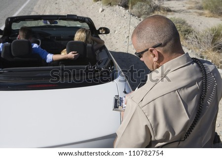 Traffic officer checking a driver's license - stock photo