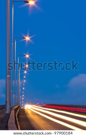 traffic on evening road with street lamps - stock photo