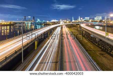 traffic on road with cityscape and skyline of portland at twilight